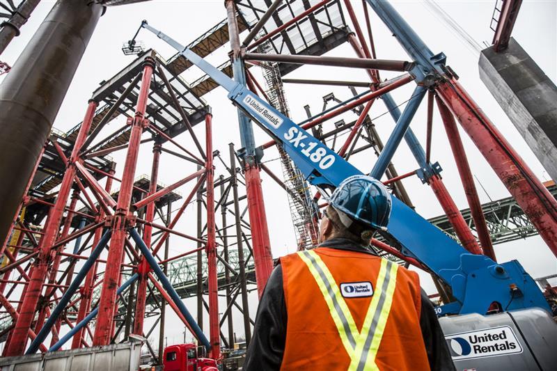 Man at job site looking at Equipment