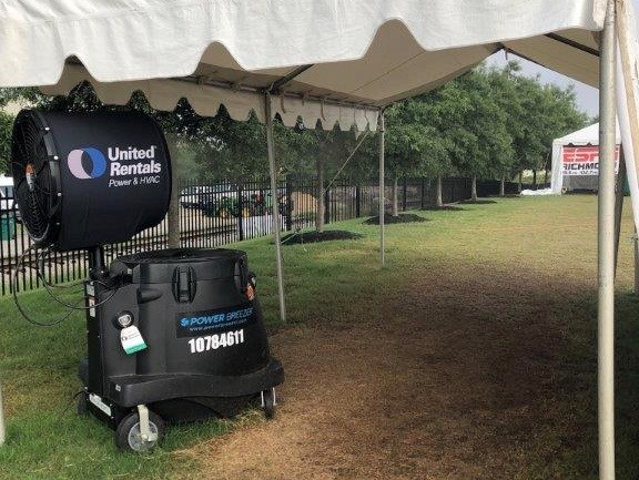 Black United Rentals Faan under a tent outside on grass