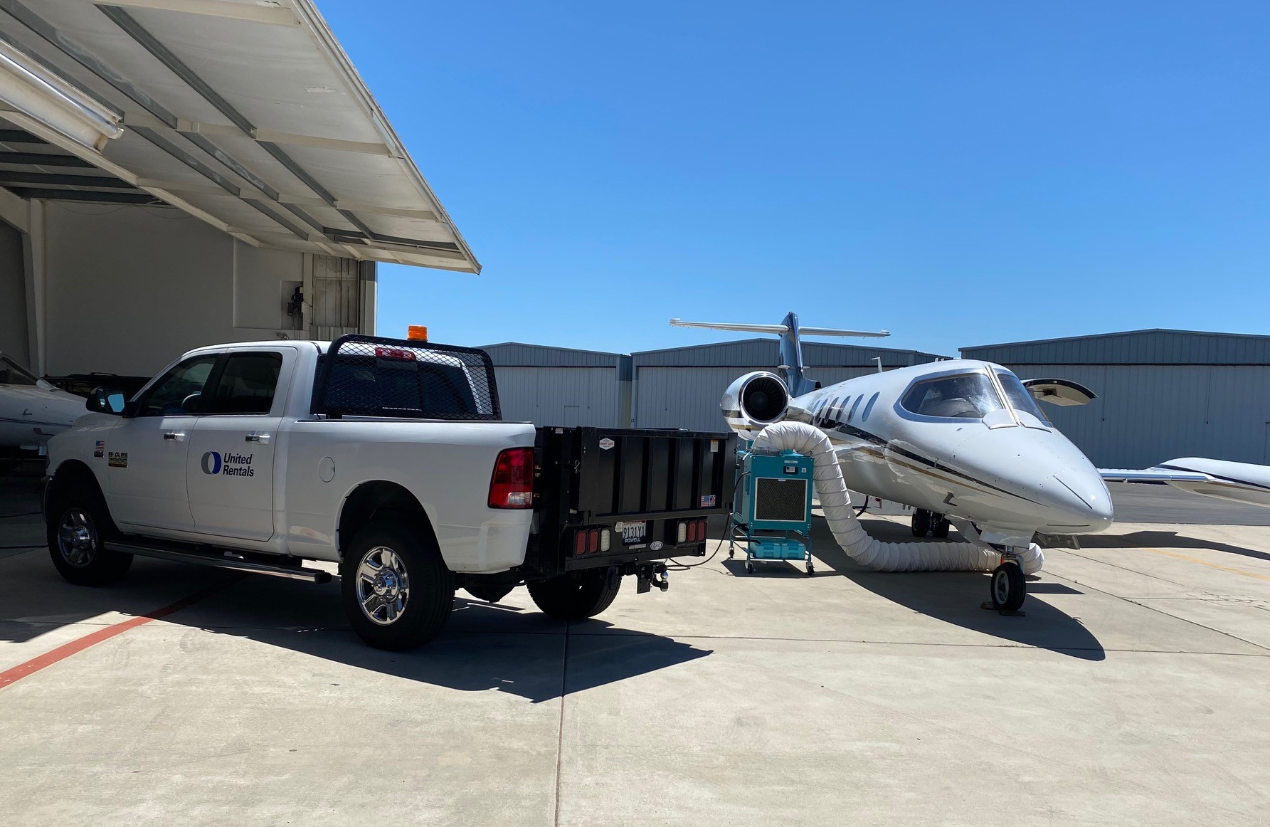 Truck parked outside a hanger next to a spot cooler being used outside a corporate jet