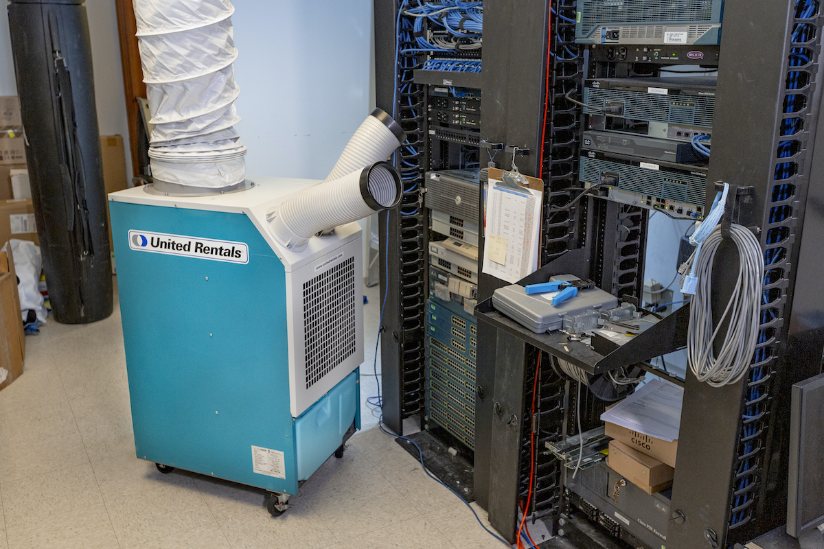 Light blue and white united rentals spot cooler in front of a server in a data center