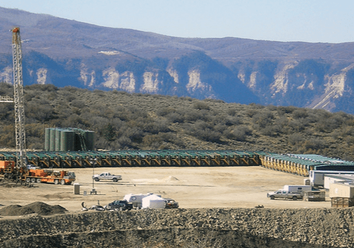 oil gas jobsite in front of mountains