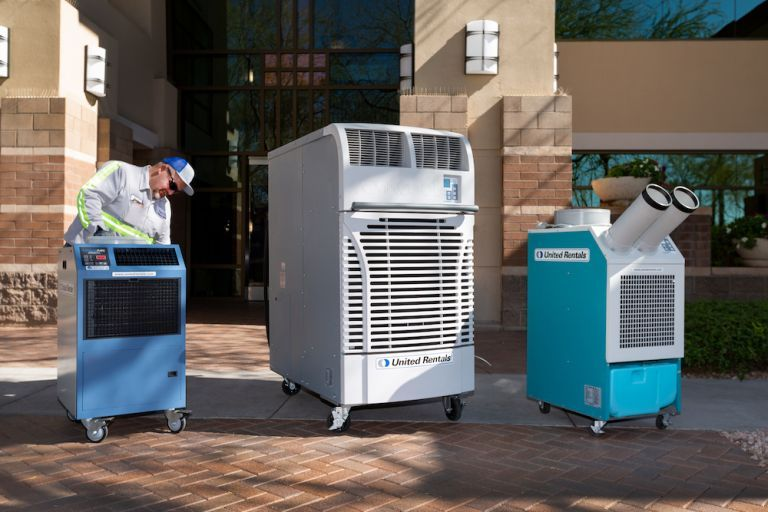 man inspecting a portable heater next to two other portable air conditioner units