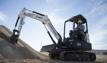 man in mini excavator near dirt pile