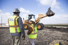 wheel loader with man and woman in PPE on jobsite