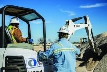 2 construction workers with mini excavator on jobsite