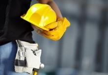 man holding hard hat wearing gloves