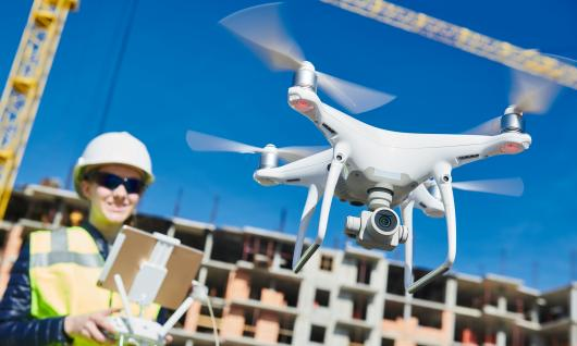 female drone pilot operating uav on construction site